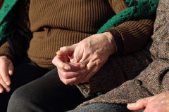 Elderly couple holding hands in a sign of love Stock Images