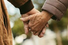 Elderly couple holding hands and walking. Close up of elderly couple holding hands and walking outdoors. Rear view of men and women holding hands of each other royalty free stock photos