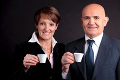 An elderly couple holding up two cups of espreso coffee. A smiling elderly couple holding up two cups of italian espreso coffee and smiling each other Royalty Free Stock Image