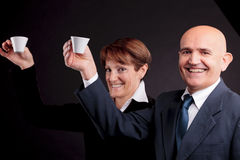 An elderly couple holding up two cups of espreso coffee. A smiling elderly couple holding up two cups of italian espreso coffee and smiling each other Royalty Free Stock Images