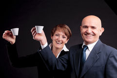 An elderly couple holding up two cups of espreso coffee. A smiling elderly couple holding up two cups of italian espreso coffee and smiling each other Royalty Free Stock Photography