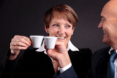 An elderly couple holding up two cups of espreso coffee. A smiling elderly couple holding up two cups of italian espreso coffee and smiling each other Royalty Free Stock Photo