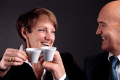 An elderly couple holding up two cups of espreso coffee. A smiling elderly couple holding up two cups of italian espreso coffee and smiling each other Stock Images