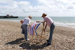 Holidaymakers erecting a deckchair on the beach. Elderly couple on holiday erect a deckchair on a windy day. Southsea southern England UK Stock Photo
