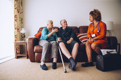 Elderly Couple with Home Carer. Elderly couple talking to their healthcare worker at home. They are sittig on the sofa in the living room Royalty Free Stock Photos