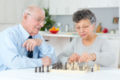 Elderly couple at home playing chess. Senior stock images