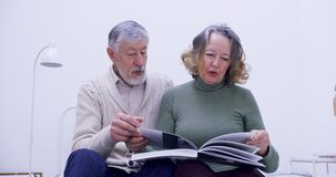 an elderly couple at home sits on a bed and reviews a large book discussing its contents