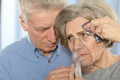 Elderly couple with inhaler. Elderly sad couple making inhalation together closeup Royalty Free Stock Photography