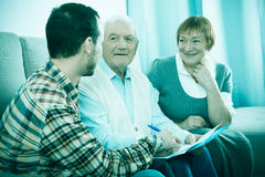 Elderly couple and insurance agent. Elderly men and agent sign life and health insurance contract at home stock images