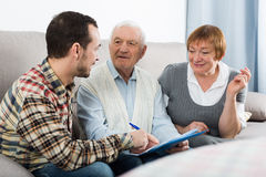 Elderly couple and insurance agent. Elderly couple and agent sign life and health insurance contract at home royalty free stock photo