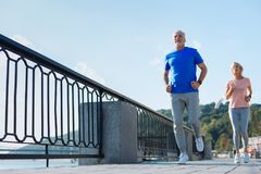 Elderly couple jogging down the bridge. Forever young. Pleasant energetic elderly men and women running down the bridge while exercising in the morning Royalty Free Stock Photos