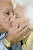 An elderly couple kissing Stock Image