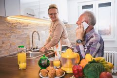 Elderly couple in the kitchen preparing breakfast royalty free stock images