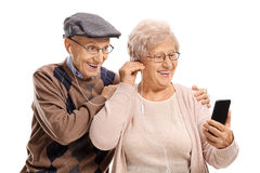 Elderly couple listening to music on a phone together Stock Photography
