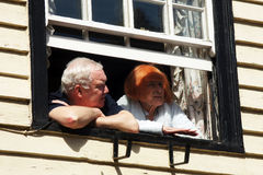 Elderly couple look out from their window Stock Images