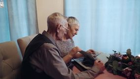 Elderly couple looking photo album. Hd stock video footage
