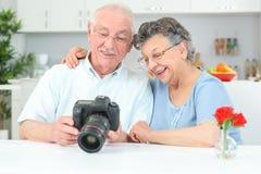 Elderly couple looking at photos on display digital camera Royalty Free Stock Image