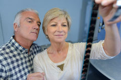 Elderly couple looking at roll film Stock Photos