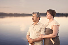 Elderly couple looking at the sunset near the lake river stock images
