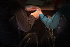Elderly Couple Love Hold Hands. An old, elderly couple are still very much in love as they hold hands while sitting in their wheelchair at the assisted living Stock Images