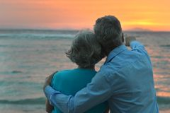 Elderly couple. In love at sunset on a summer evening watching sea stock images