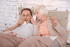 Elderly couple lying on bed with cold. How could we. Very sick elderly couple lying on bed covered with blankets and blowing their noses Stock Photo