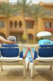 Elderly couple lying by pool Stock Photos
