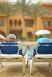Elderly couple lying by pool Stock Photos