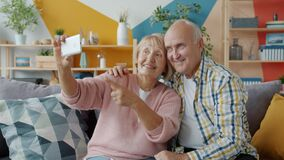 Elderly couple man and woman taking selfie with smartphone camera at home