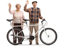 Elderly couple of a man and woman with a tandem bicycle waving. Full length portrait of an elderly couple of a men and women with a tandem bicycle waving stock photo