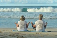 Elderly couple meditate on beach Stock Image