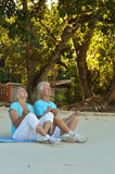 Elderly couple meditating. Together on sandy beach Royalty Free Stock Photo