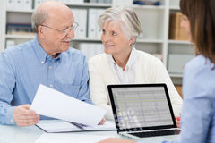 Elderly couple in a meeting with an adviser. Discussing a document as she watches across the desk in her office Royalty Free Stock Photos