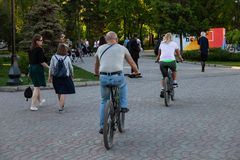 Elderly couple men and women ride bicycles during a walk in the park among a large number of people at the weekend on a warm royalty free stock image