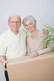 Elderly couple moving house. Standing arm in arm with a brown cardboard carton smiling happily in anticipation of a new beginning royalty free stock photos