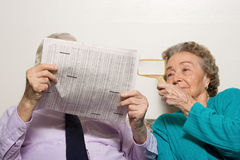 Elderly couple with newspaper Royalty Free Stock Photo