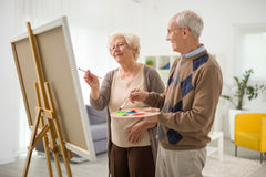 Elderly couple painting on a canvas. Elderly couple having fun together and painting on a canvas at home royalty free stock photography