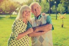 Elderly couple on park background. Royalty Free Stock Image