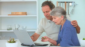 Elderly couple paying something on internet Stock Photography