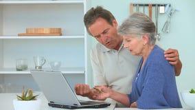 Elderly couple paying something on internet stock footage