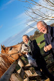 Elderly couple petting a horse in a paddock. Elderly couple laughing and having fun petting a horse in a paddock on a cold sunny winter day as they enjoy the stock photography