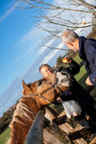 Elderly couple petting a horse in a paddock Royalty Free Stock Image