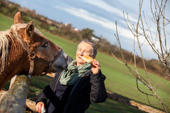 Elderly couple petting a horse in a paddock. Elderly couple laughing and having fun petting a horse in a paddock on a cold sunny winter day as they enjoy the Royalty Free Stock Images