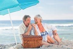 Elderly couple picnicking on the beach stock photo