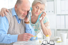 Elderly couple with pills Stock Images