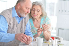 Elderly couple with pills Royalty Free Stock Images