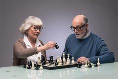 Elderly couple playing chess. Studio shot on gray background royalty free stock photo