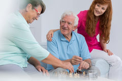 Elderly couple playing chess. Elderly married couple playing chss with good carer stock photography