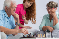 Elderly couple playing chess. Young caregiver looking at elderly couple playing chess royalty free stock photography