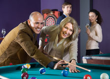 Elderly couple playing a game of billiards. young couple drinkin Stock Images